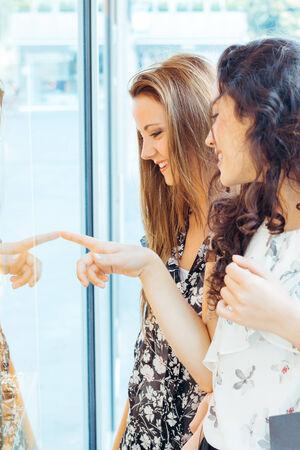 Beautiful shopping girls looking at a shop window photo
