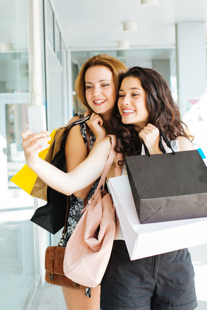 Shopping girls full of bags making a selfie out of a shop photo