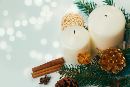 Christmas candles and ornaments over light background photo