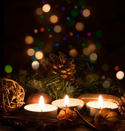 christmas spice: Christmas candles and ornaments over dark background with lights Stock Photo