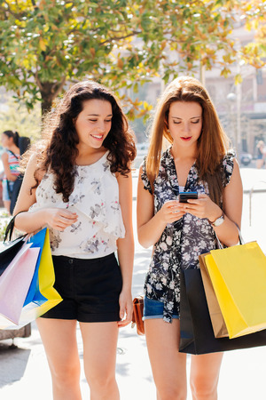 Shopping girls reading a mobile message in the street