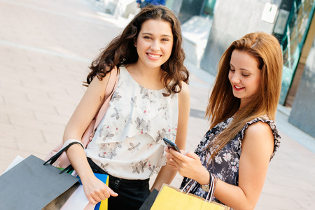 cute teen girl: Happy shopping girls with bags standing on the street to text on the smartphone