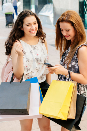 Happy shopping girls with bags standing on the street to text on the smartphone