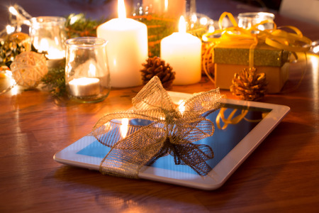 fiestas electronicas: Regalo de la Navidad de la tableta digital con velas en la mesa de noche