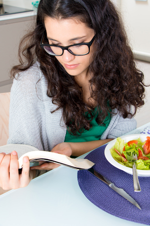 Pretty girl with horn rimmed glasses reading a book while eating salad in the kitchen photo