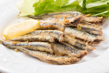Fried anchovies with lettuce salad and lemon in a dish