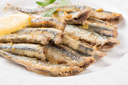 anchovy fish: Fried anchovies  with parsley and lemon in a dish close up Stock Photo