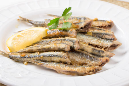 smelt: Fried anchovies  with parsley and lemon in a dish