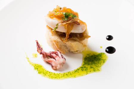 Squid with caramelized onion, parsley a nd some drops of vinegar syrup over a bread slice, called in the Basque Country as Pelayo squids