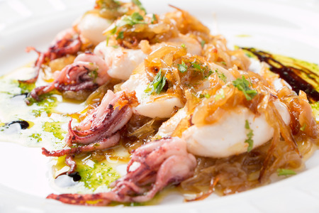 Squids with caramelized onion, parsley a nd some drops of vinegar syrup, called in the Basque Country as Pelayo squids photo