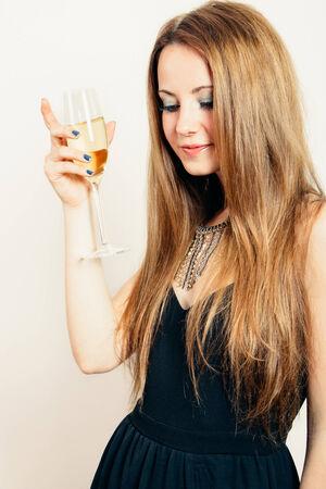 jovenes tomando alcohol: Feliz mujer rubia y hermosa en un vestido negro de fiesta con una copa de champ�n Foto de archivo