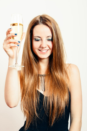 anniversary sexy: Happy and beautiful blond woman in a party black dress with a glass of champagne