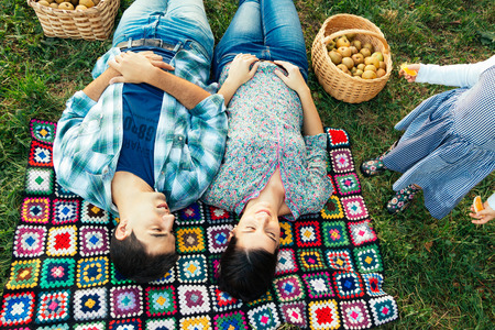Loving couple resting on a crocheted blanket on the grass in autumn after picking apples. Todler demands attention. Top view.