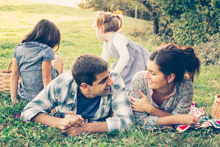 Happy family of four lying in the grass in autumn. The couple looking at eachother lovingly as the girls play. Warm effect added. Imagens