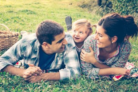 apoyo familiar: Familia feliz de tres tendido en la hierba en otoño. Efecto de calentamiento agregó.