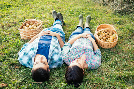 Couple resting on the grass in autumn after picking apples enjoying nature photo