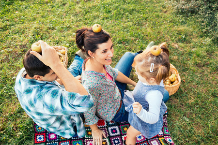 Family lying on grass playing with apples on  head after picking photo