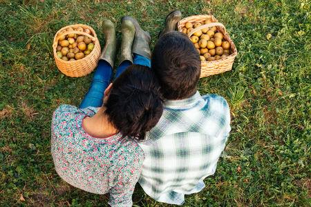 botas de lluvia: Amante de la pareja sentada en el c�sped en oto�o despu�s de recoger manzanas. Vista superior Foto de archivo