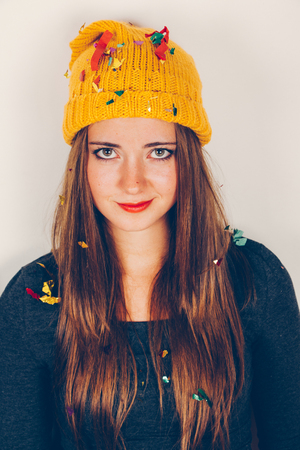 jaded: Funny girl with yellow wool cap in a boring party with confetti over head. Filter effect added.