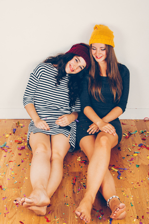 Funny girl friends resting after a party sitting on the floor full of confetti