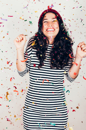 Laughing girl with striped dress and wool cap under a rain of confetti. Filter effect added. Filter effect added. Foto de archivo