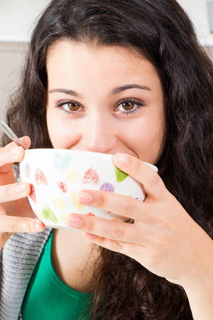 Happy teen girl with beautiful brown eyes drinking from a bowl maybe milk or soup