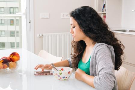 fille triste: Serious jeune femme en utilisant son téléphone intelligent tout en ayant le petit déjeuner dans une cuisine moderne Banque d'images
