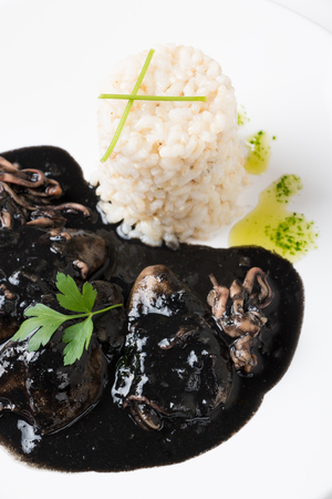 Squid in its own ink with brown rice and parsley sauce. Traditional Spanish recipe