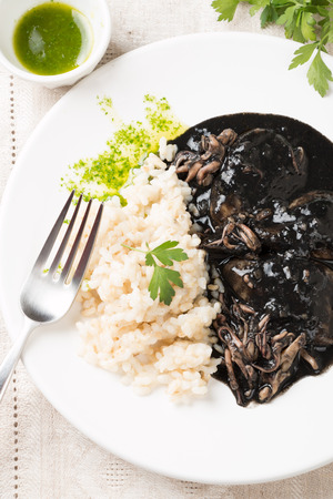 san sebastian: Squid in its own ink with brown rice and parsley sauce. Traditional Spanish recipe