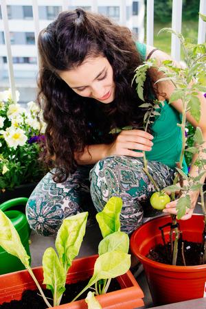 젊은 여자 발코니에 냄비에 그녀의 작은 부엌 정원 자랑
