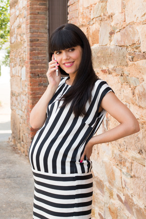 Stylish pregnant woman with striped dress on the phone photo