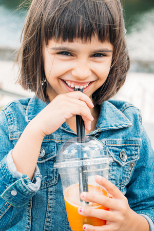 Happy little girl drinking a fruit smoothie in the street