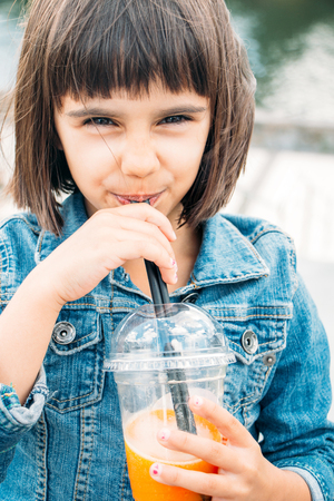 take away: Little girl drinking a fruit smoothie in the street Stock Photo
