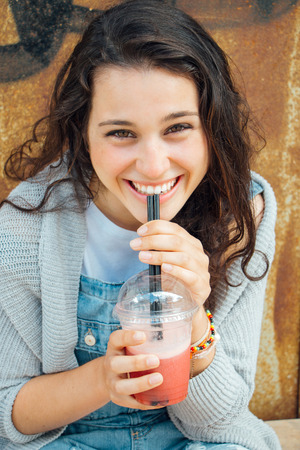 Beautiful and happy teen girl drinking a fruit smoothie in the street Stockfoto