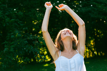 Happy woman with arms outstretched looking up enjoying the sun and nature