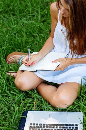 sandalias: Niña sentada en la hierba que trabaja con un ordenador portátil y un ordenador portátil. Enfoque en la mano Foto de archivo