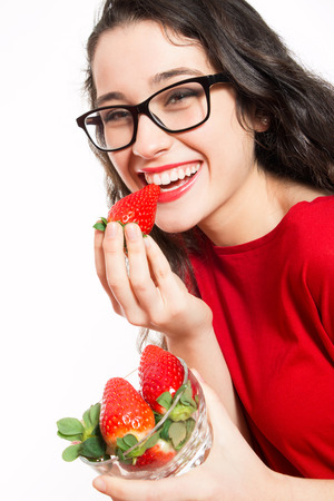 Happy and beautiful woman with eyeglasses eating strawberries