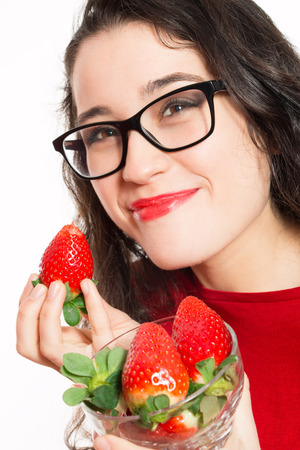 black rimmed: Funny woman with eyeglasses tasting strawberries with delight