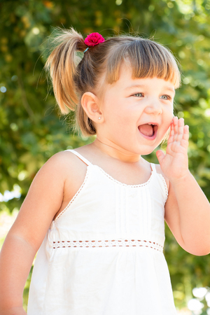 kids dress: Cute and pretty little girl calling hand in mouth
