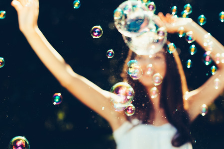 Girl with arms raised dancing with bubbles outdoors. Girl is defocused Imagens