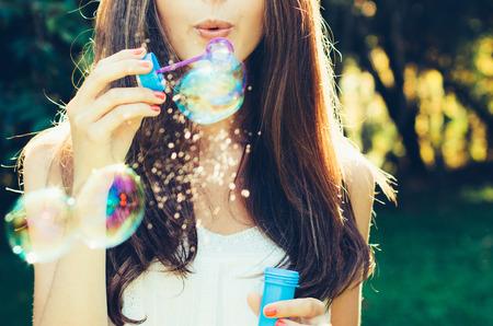 bulles de savon: Fille soufflant des bulles en plein air. Concentrez-vous sur les l�vres. Banque d'images