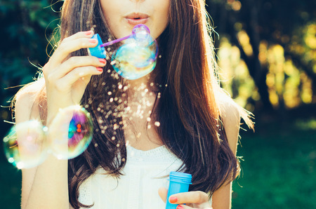 Girl blowing bubbles buiten. Focus op de lippen. Stockfoto