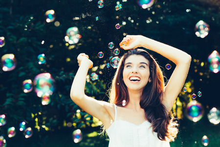 Beautiful young woman having fun with bubbles outdoors Foto de archivo
