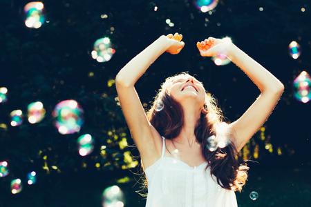 burbujas jabon: Mujer joven que se divierte con burbujas al aire libre