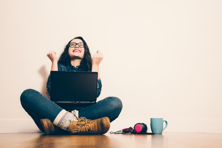 Girl sitting on the floor with a laptop raising his arms with a look of success