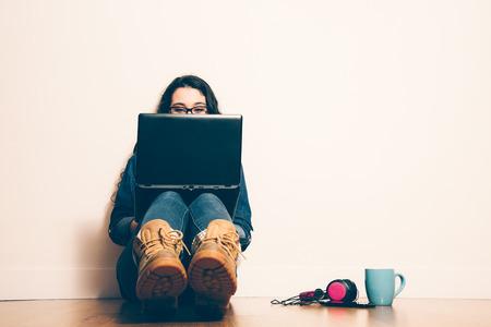 koncentrovaný: Dívka sedí na podlaze s laptop při pohledu na obrazovku koncentrovaný. Filter efekt dodal.