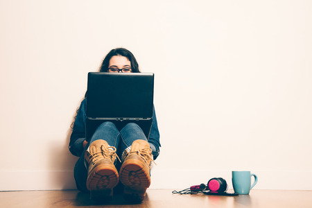 woman sitting with laptop: Girl sitting on the floor with a laptop looking at screen concentrated. Filter effect added. Stock Photo