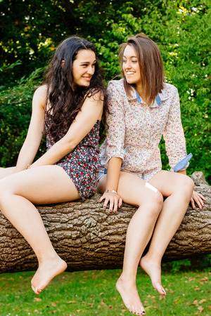 barefoot teens: Cute and funny girl friends sitting on a tree trunk Stock Photo