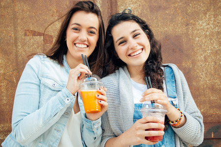 Funny and cute girls having a fruit smoothie in the street Archivio Fotografico