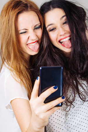 Girl friends making a funny selfie with tongues out photo